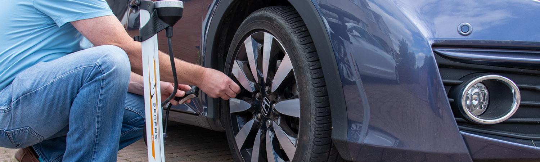 man checking tyre pressure